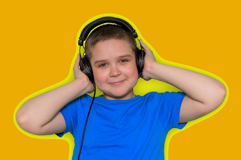 beautiful cute young boy in blue t-shirt with big black headphones isolated on yellow vibrant background royalty free stock image