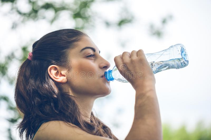 Portrait of beautiful dark-haired girl drinking water at summer stock images