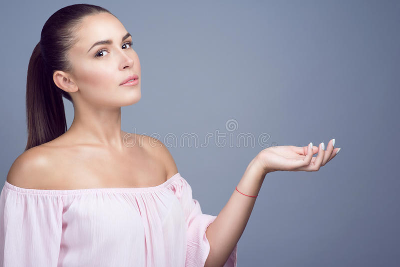 Portrait of beautiful dark-haired girl with perfect skin and nude make up showing empty palm proposing a product. Advertising gestures concept. Copy-space stock photography