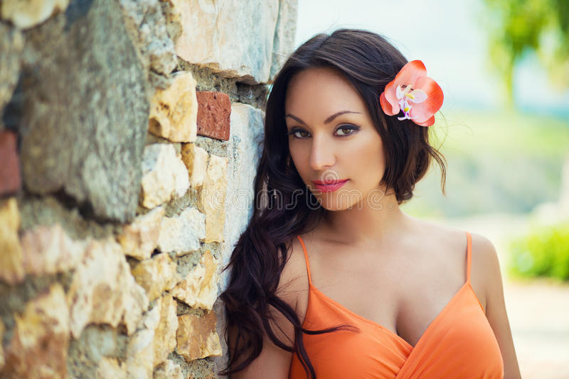 Portrait of beautiful dark-haired smiling girl against the backdrop of medieval stone buildings in the town of Altos de Chavon stock photo