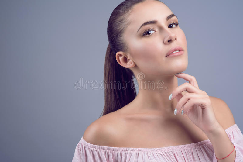 Portrait of beautiful dark-haired young model with perfect skin and wet nude make up on grey background stock photo