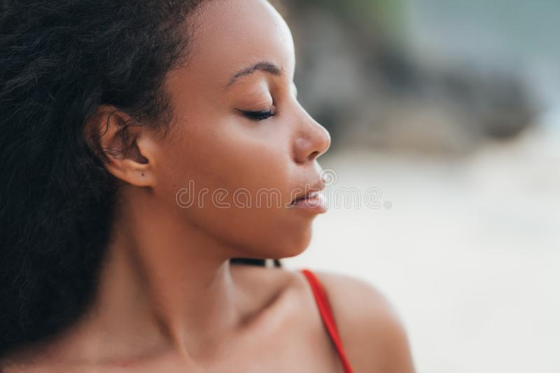 Portrait of beautiful dark skinned girl with closed eyes posing on beach. Sensual afro american model with curly hair stock image