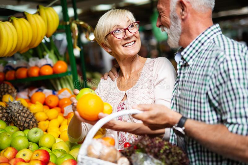 Portrait of beautiful elderly couple in market buing food royalty free stock images