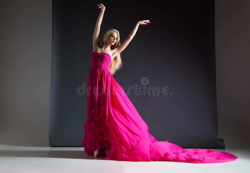 Portrait of beautiful and elegant blonde woman posing in pink dress stock image