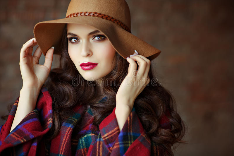Portrait of a beautiful elegant woman brunette with brown eyes w. Earing a hat, close-up royalty free stock image