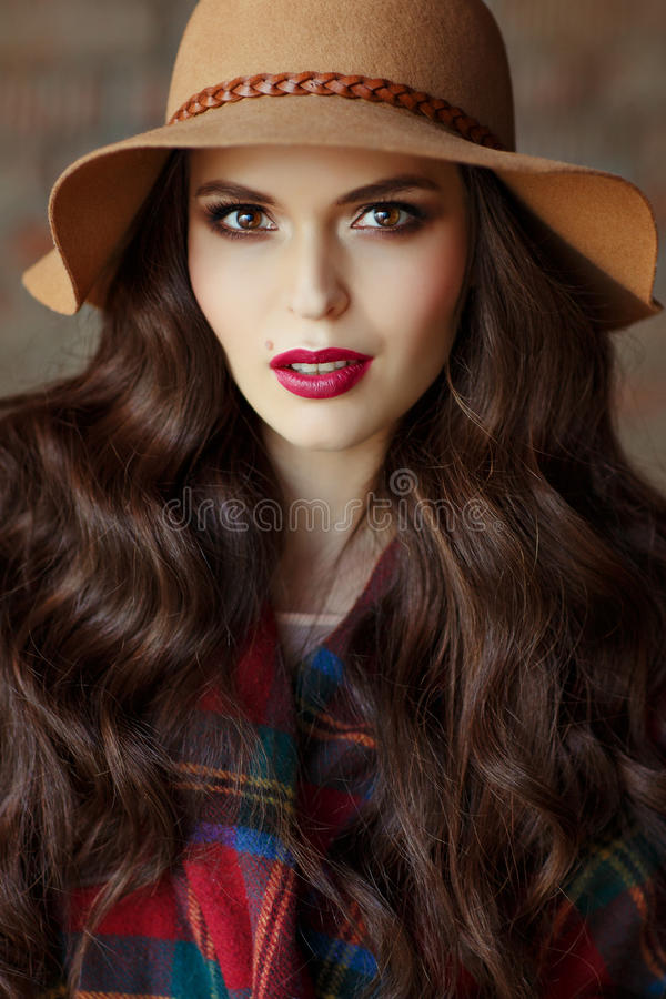 Portrait of a beautiful elegant woman brunette with brown eyes w. Earing a hat, close-up royalty free stock images