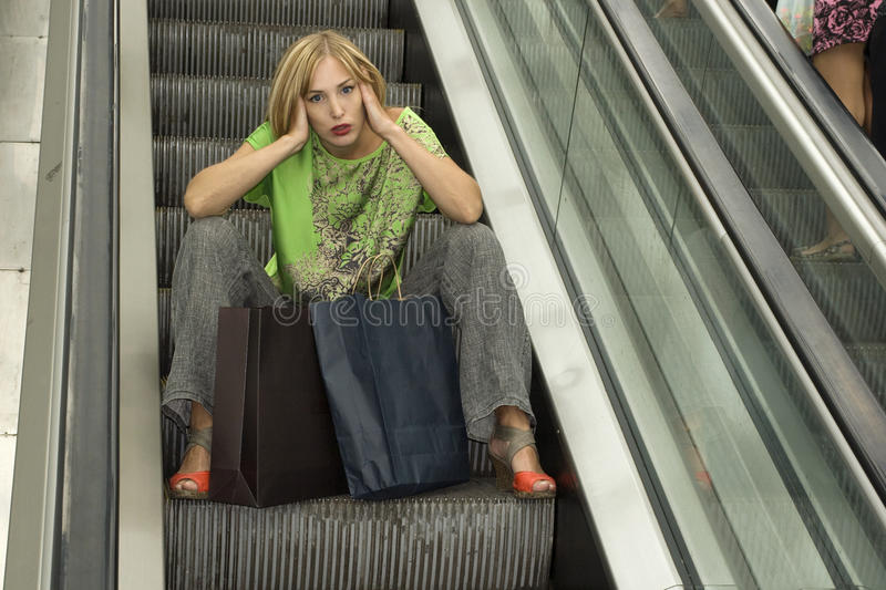 Portrait of a beautiful elegant young blonde woman in the mall escalator with bags. stock photo