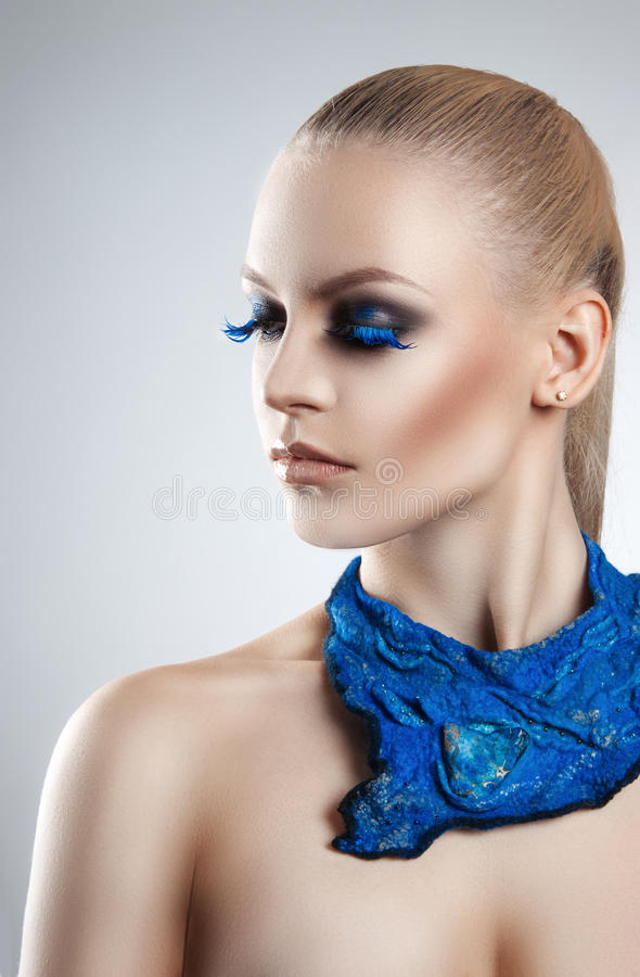 Portrait of a beautiful evening makeup. Blue eyelashes. The girl blue neckerchief royalty free stock photography