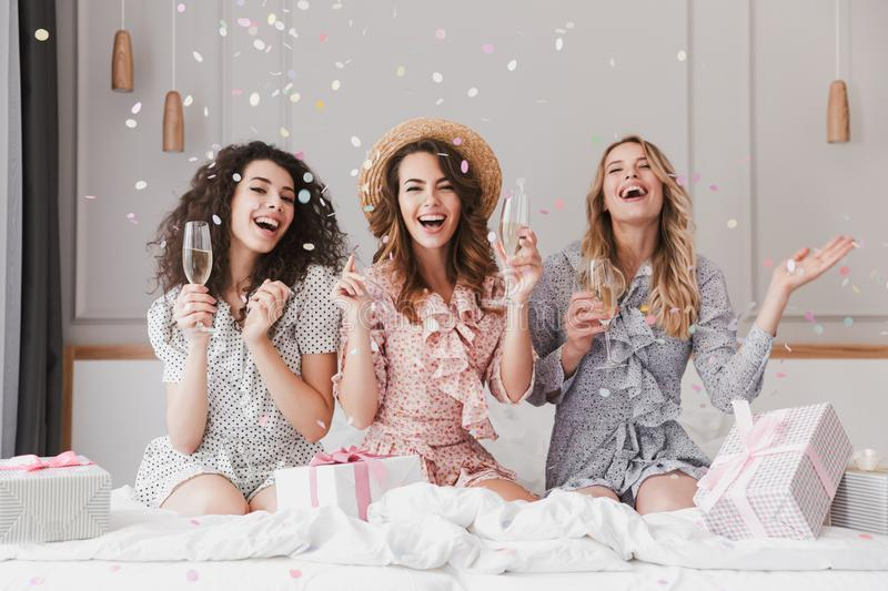 Portrait of beautiful excited women 20s wearing dresses celebrating bridal shower in posh apartment, with champagne and falling c. Portrait of beautiful excited stock photography
