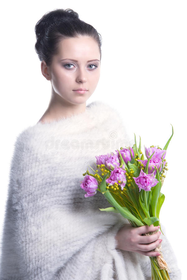 Beauty woman in warm white woolen poncho with spring flowers in her hands. Portrait of beautiful face and pure skin brunette woman wearing white knitted woolen royalty free stock photo