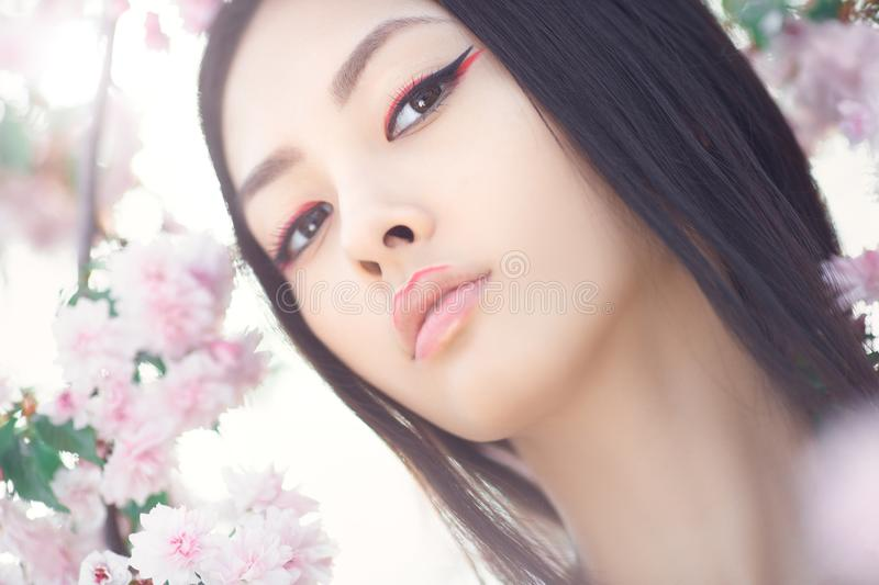 Portrait of a beautiful fantasy asian girl outdoors against natural spring flower background. Gorgeous fantasy girl face close-up against nature beauty stock image