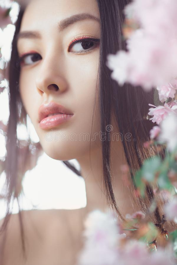Portrait of a beautiful fantasy asian girl outdoors against natural spring flower background. Perfect model with creative vivid makeup and pink lipstick on lips stock photography