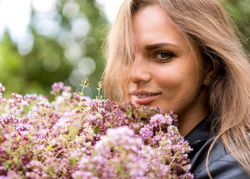 Portrait of a beautiful fashion girl with a bouquet of lilac flowers on the street royalty free stock image