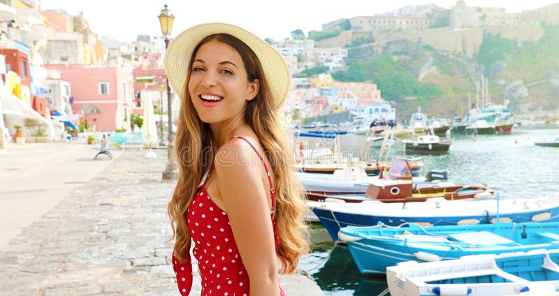 Portrait of beautiful fashion girl in Procida, Italy. Attractive young woman with red dress and hat walks along the harbor of. Procida Island in Italy royalty free stock photography