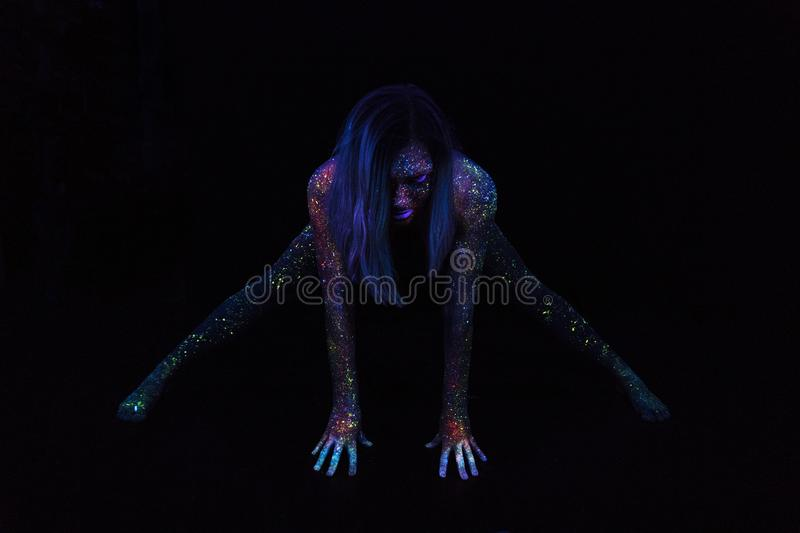 Portrait of Beautiful Fashion Woman Doing Yoga in Neon UF Light. Model Girl with Fluorescent Creative Psychedelic MakeUp royalty free stock images