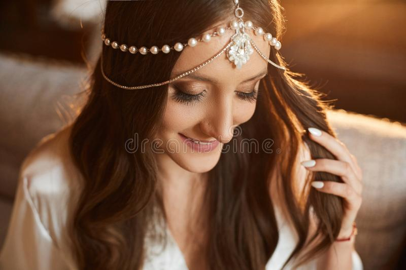 Portrait of beautiful and fashionable brunette model girl with charming smile, with trendy jewelry on her head and with royalty free stock images