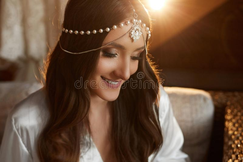 Portrait of beautiful and fashionable brunette model girl with charming smile, with trendy jewelry on her head and with stock photos