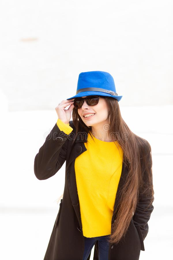 Portrait of a beautiful fashionable stylish woman in bright yellow sweater and blue hat. Street style shooting.  stock photos
