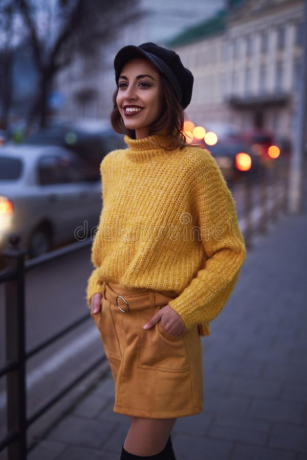Beautiful fashionable woman in bright yellow sweater and skirt walking and posing outdoors royalty free stock photo