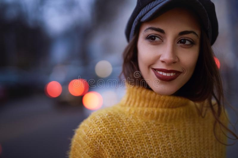 Beautiful fashionable woman in bright yellow sweater and skirt walking and posing outdoors. Portrait of a beautiful fashionable stylish woman in bright yellow royalty free stock images