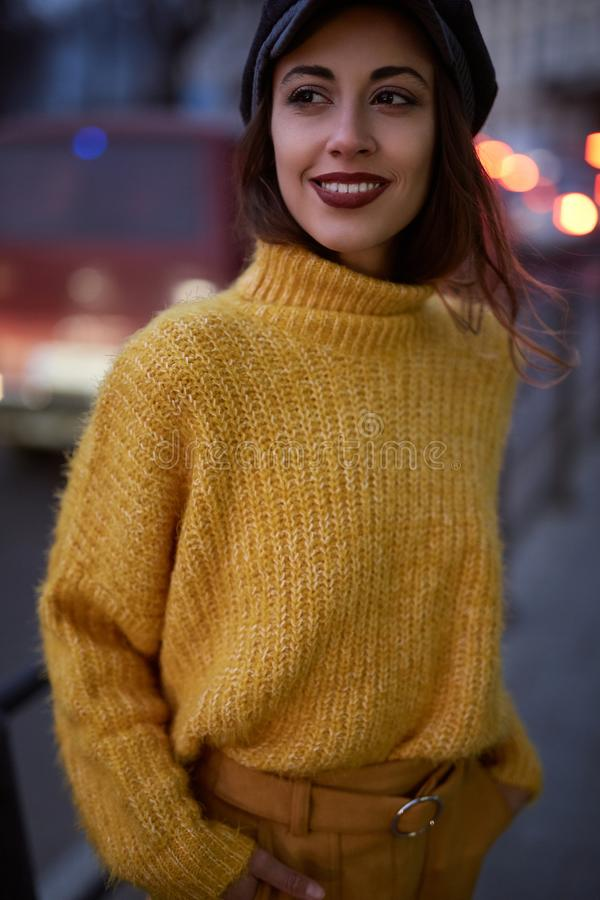 Beautiful fashionable woman in bright yellow sweater and skirt walking and posing outdoors stock photography