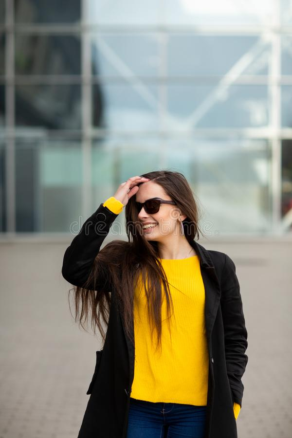 Portrait of a beautiful fashionable stylish woman in bright yellow sweater. Street style shooting.  stock photography