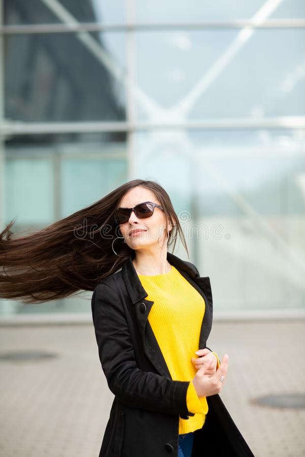 Portrait of a beautiful fashionable stylish woman in bright yellow sweater. Street style shooting.  royalty free stock photography