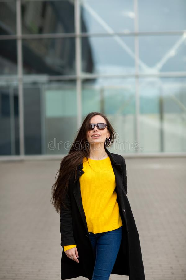 Portrait of a beautiful fashionable stylish woman in bright yellow sweater. Street style shooting.  royalty free stock image
