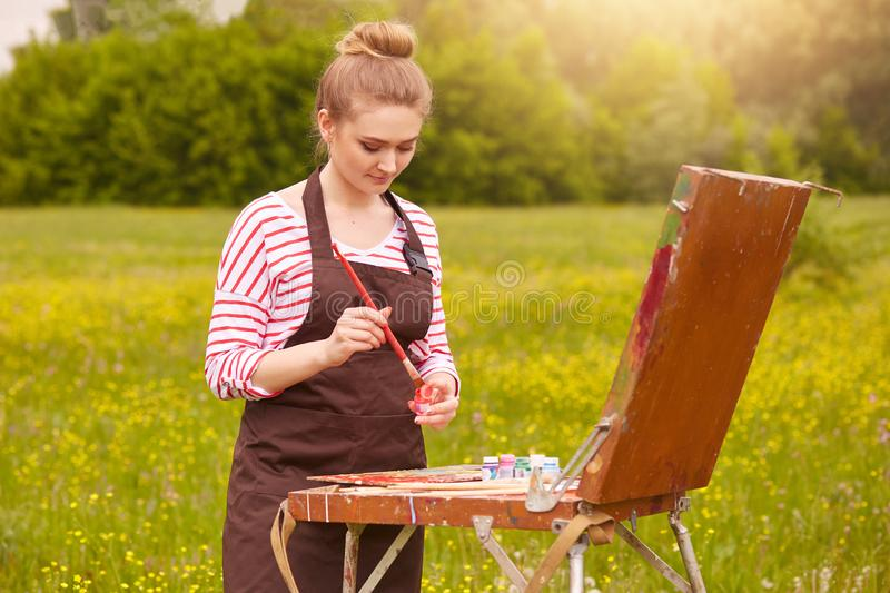 Portrait of beautiful female looking at watercolour samples on convas, mixed colours, has concentrated facial expression, woman. Wears casual clothes, has fair stock images