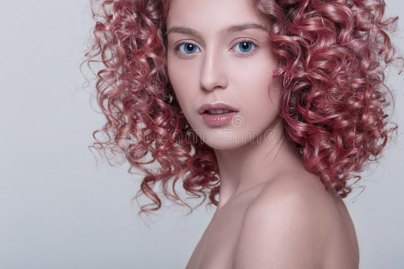 Portrait of beautiful female model with red curly hair royalty free stock photography