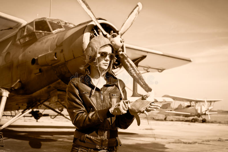 Portrait of beautiful female pilot. With plane behind. Sepia photo stock images