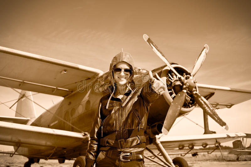 Portrait of beautiful female pilot with plane behind. Sepia photo stock photography