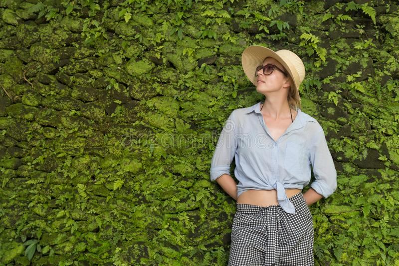 Portrait of a beautiful female traveler. Smiling young woman in summer hat wearing sunglasses, standing in front of lush stock image