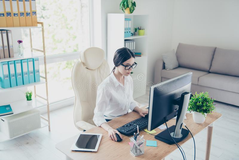 Portrait of beautiful focused asian young businesswoman sitting at bright modern work station and typing on laptop. Attractive cha stock photo