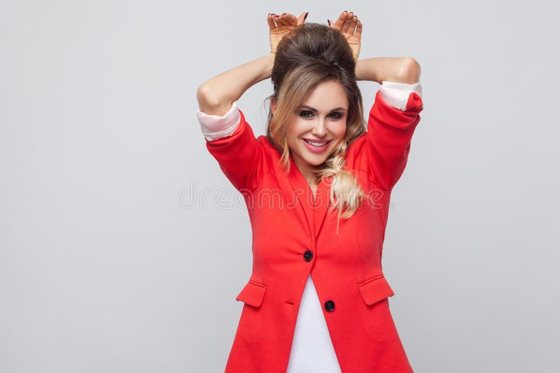 Portrait of beautiful funny business lady with hairstyle and makeup in red fancy blazer, standing, toothy smiling and looking at. Camera with bunny gesture royalty free stock photography