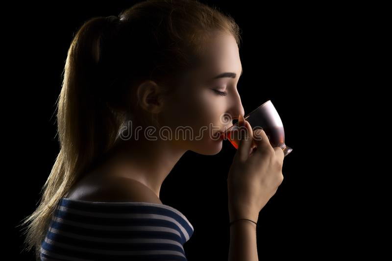 portrait of a beautiful gir drinking tea, woman`s face with eyes closed on a black background royalty free stock image