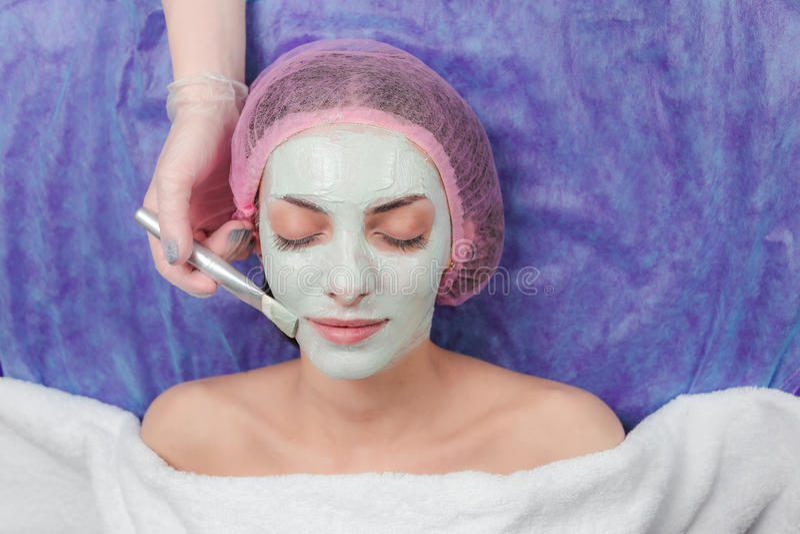 Portrait of beautiful girl applying facial clay mask beauty treatments royalty free stock photo