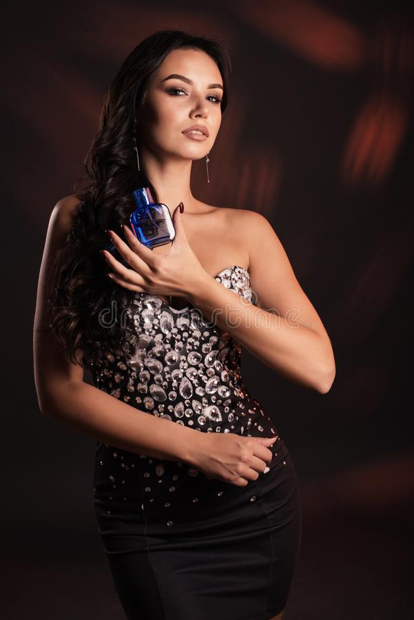 Portrait of a beautiful girl in a black dress with spirits in hands stock images