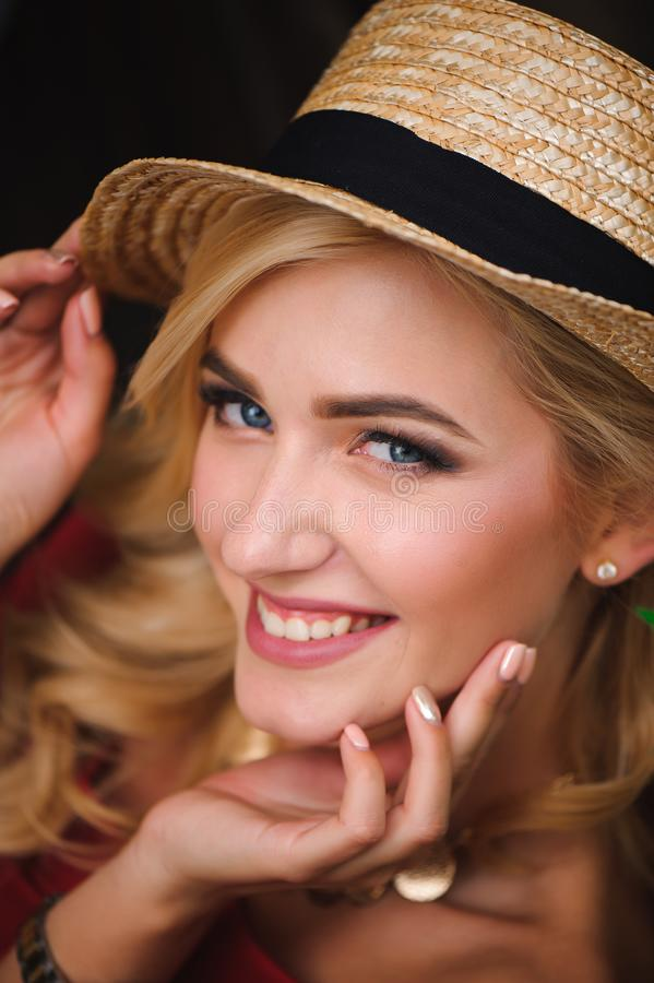 Portrait of a beautiful girl with blond hair. Stylish girl is sitting on a park bench. Fashion model. royalty free stock photography