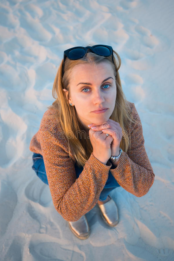 Portrait of beautiful girl, blonde who sits on the beach royalty free stock photo