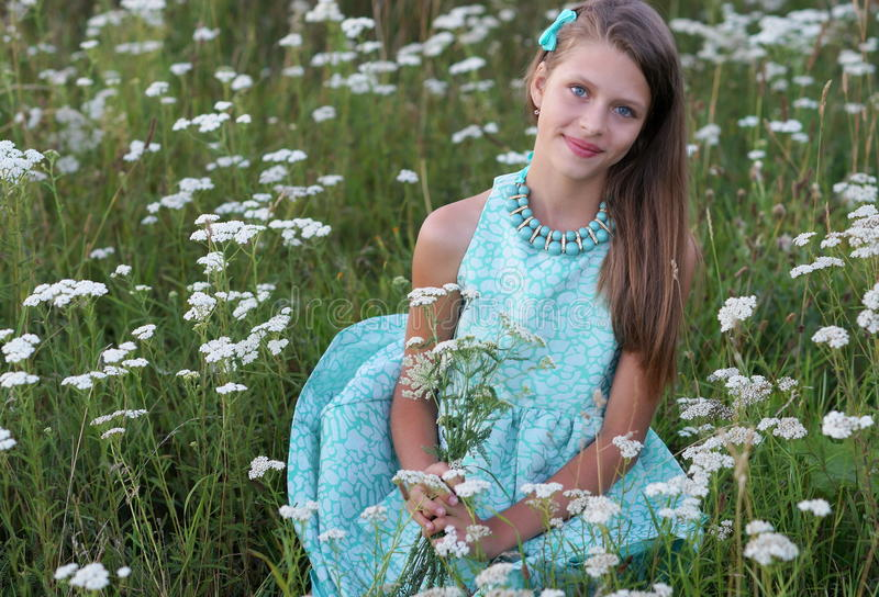 Portrait of a beautiful girl in a blue dress and ornaments posing outdoors. Among white flowers royalty free stock photo