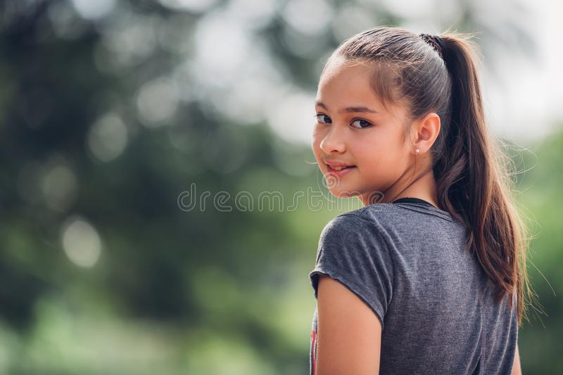 Portrait of a beautiful girl in the bokeh of leaves is a green. Backdrop of nature, The girl smiled happily at the camera royalty free stock photography