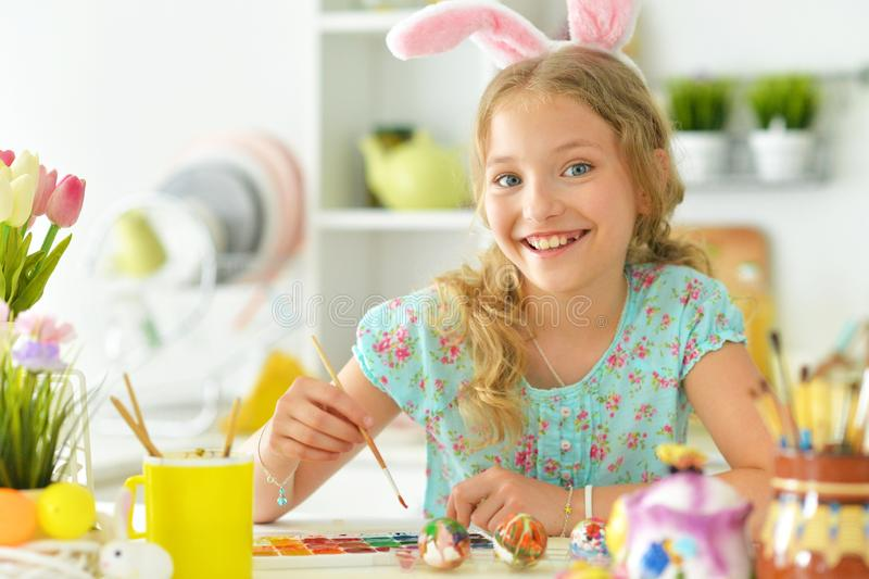 Portrait of beautiful girl in bunny ears painting eggs for Easter holiday royalty free stock photo