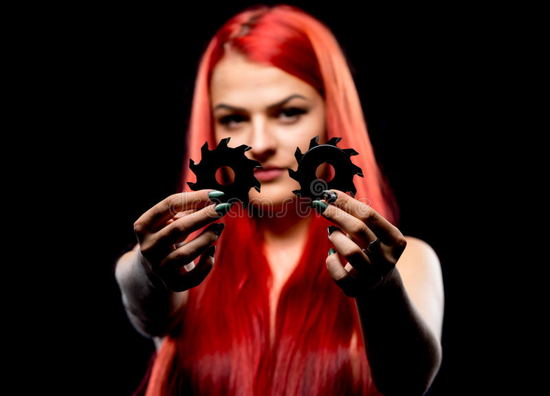 Portrait of beautiful girl with circular saw blade. Bretty naked woman, long red hair, nude body, sawblade, dark background royalty free stock photography