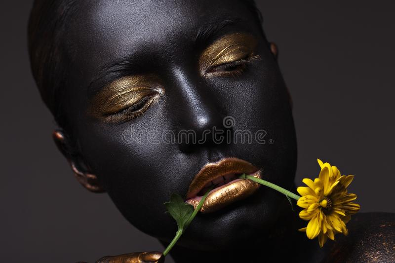 Portrait of a beautiful girl with a creative make-up, close-up. With a yellow flower in the mouth stock photo