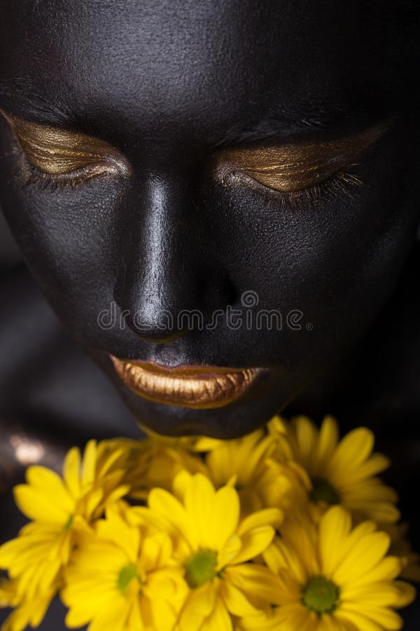 Portrait of a beautiful girl with a creative make-up, close-up. With yellow flowers royalty free stock photos