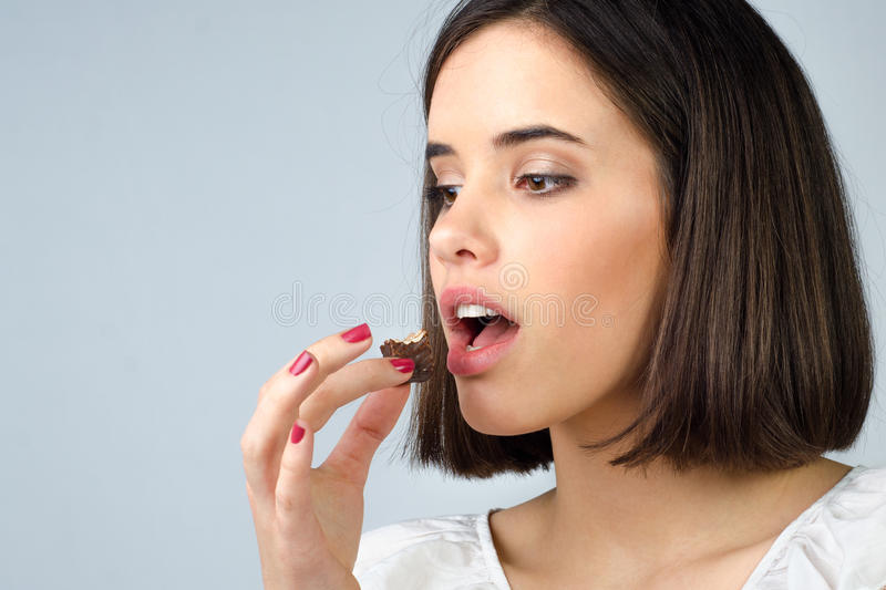Portrait of the beautiful girl eating chocolate cookies isolated royalty free stock photography