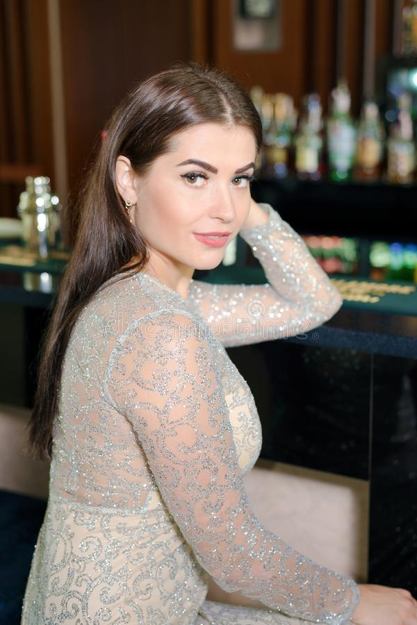 Portrait of beautiful girl in an evening dress. Brunette woman posing in bar restaurant stock images