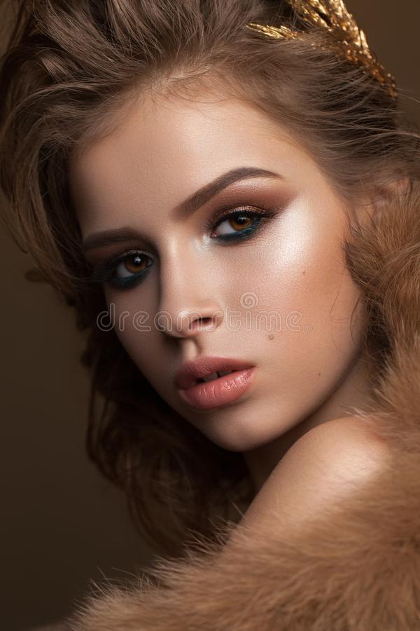 Portrait of a beautiful girl with evening make up, bright green eyeliner, volume hairdo and gold accessories in hair stock photos
