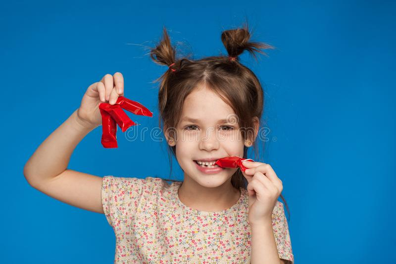 Portrait of a beautiful girl of five years old with an interesting hairstyle and with candies in her hands on a blue background stock image